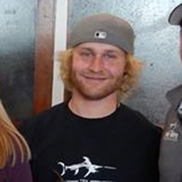 blonde guy smiling with hat on backwards