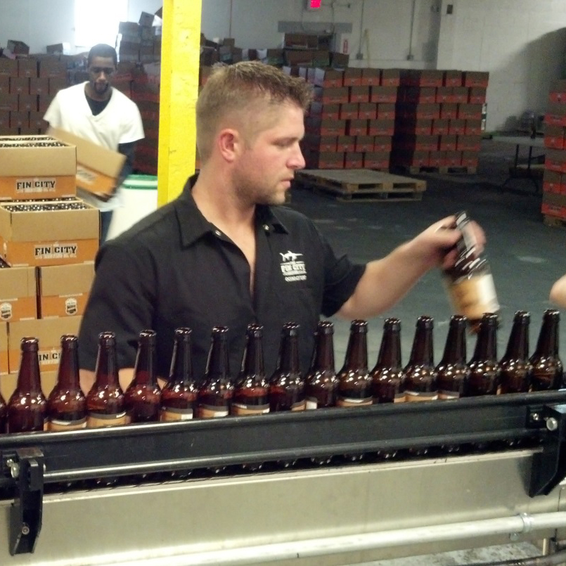 man in fin city brewing co brewery on bottle assembly line
