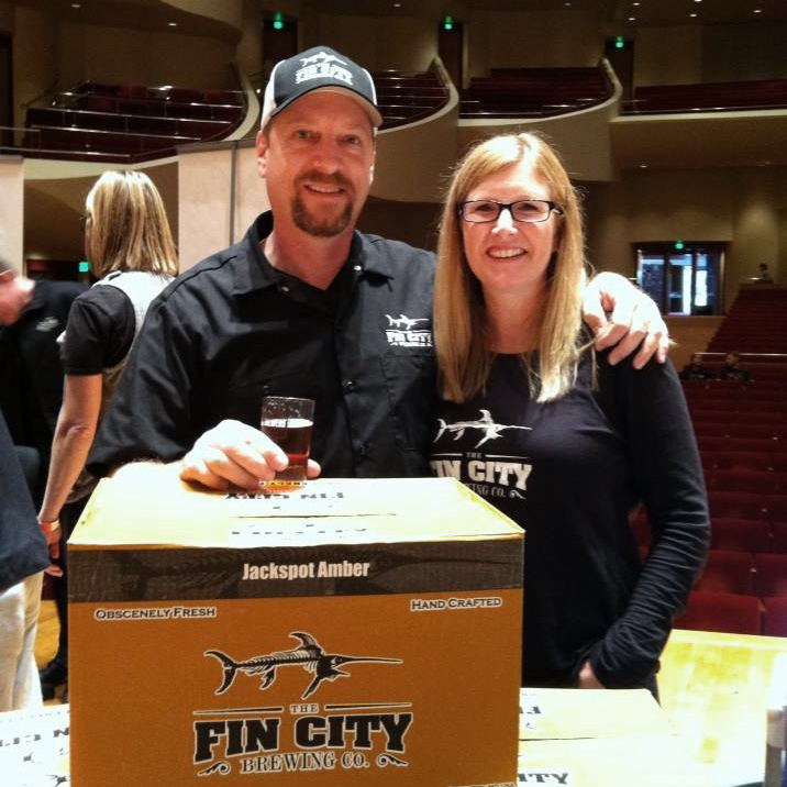 man and woman wearing fin city apparel holding fin city case of beer